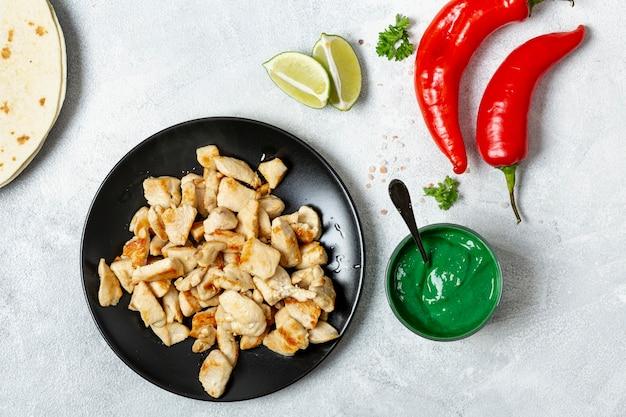 Kippenschotel dichtbij peper, groene saus en gesneden kalk