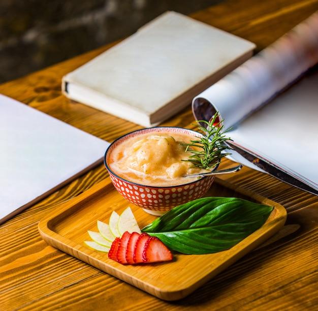 Kippensoep in bouillon met verse rozemarijnbladeren en groene oregano.