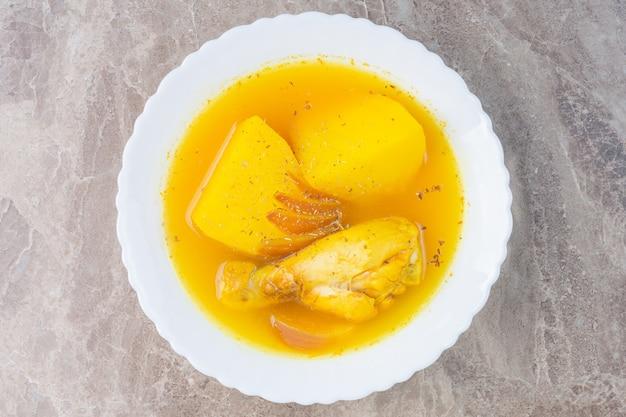 Kippensoep in een kom, op het marmer.