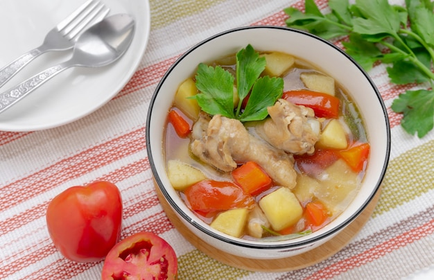 Kippensoep met aardappelen op tafel in bovenaanzicht