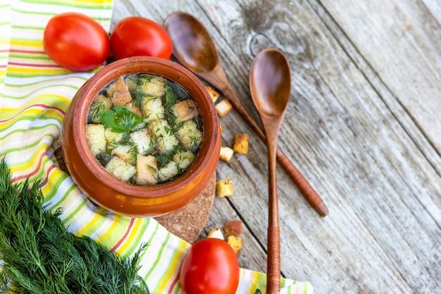 Kippensoep met croutons op een houten achtergrond met kruiden en diverse smaakmakers.