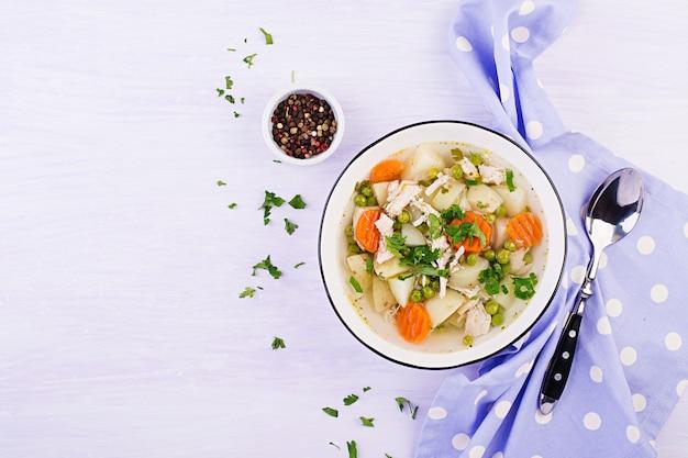 Kippensoep met groene erwten, wortelen en aardappelen in een witte kom