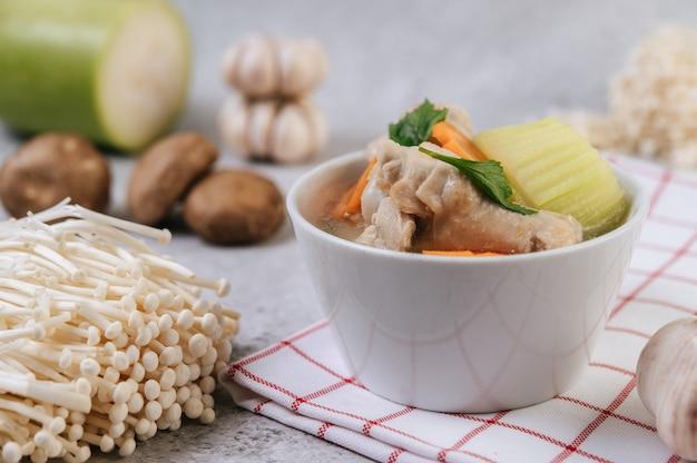 Kippensoep met maïs, shiitake-paddenstoel, enoki-paddenstoel en wortel.