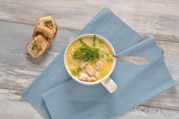 Kippensoep. warme wintersoep met kip en aardappelen. chowder soep met kip en aardappelen. verse romige soep met kip en groenten in witte kom op de houten achtergrond. gezond eten