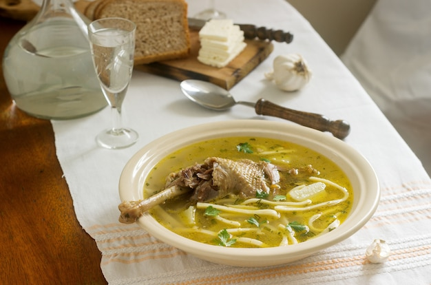 Kippensoep zama traditionele moldavische of roemeense soep geserveerd met kaas, brood en knoflook. rustieke stijl.