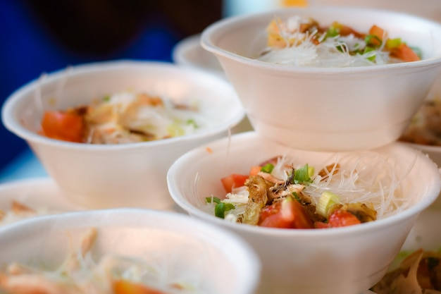 Kippensoepschotel geserveerd in piepschuimkom daar geraspte kippenvleestomaten en rijstnoedels