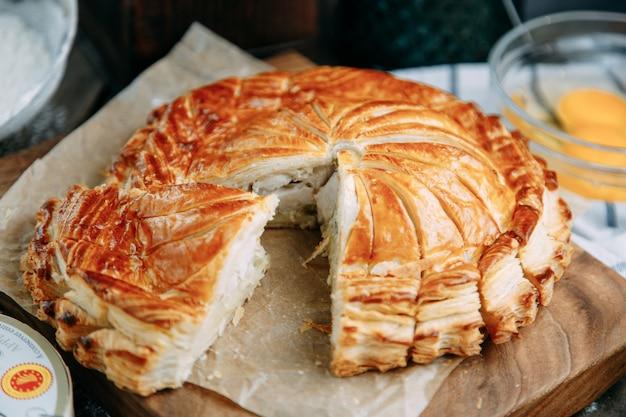 Kippentaart met bladerdeeg aardappelen. ronde taart op een donkere houten achtergrond.