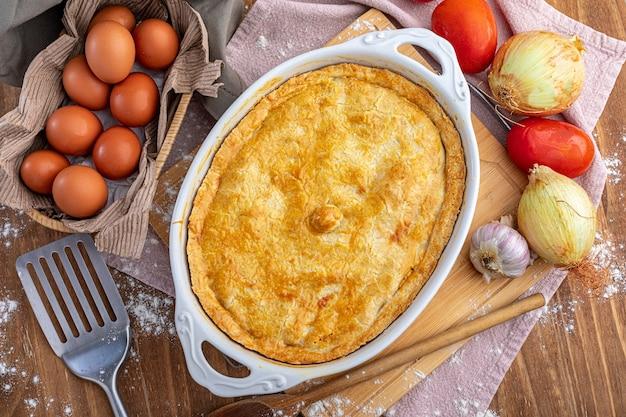 Kippentaart op het bord en groenten op de houten tafel