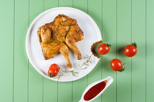 Kippentabak met tomatensaus, rozemarijn en tomaten op een mooie witte plaat op een groene tafel. gegrilde kip.