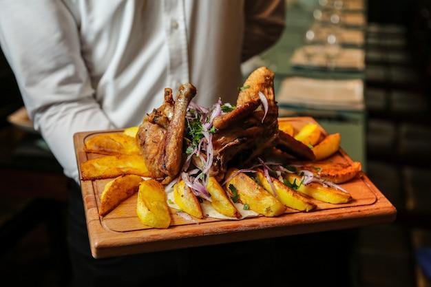 Kippentabaka op de houten raad met de eigengemaakte aardappelui maakt zijaanzicht groen