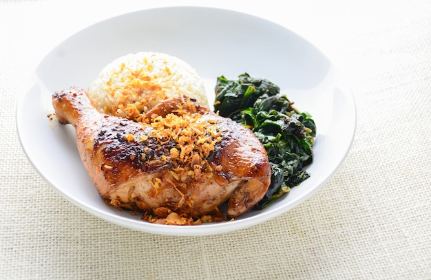 Kippentrommelstok gemarineerd met pittige chilisaus en kruiden, geserveerd met gekookte rijst en spinash.