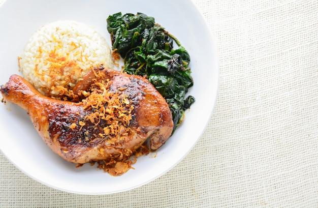 Kippentrommelstok gemarineerd met pittige chilisaus en kruiden, geserveerd met gekookte rijst en spinazie.