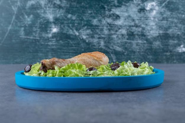 Kippentrommelstok, olijven en sla op blauw bord.