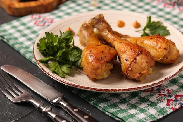 Kippentrommelstokken in mosterdmarinade worden op een plaat op donkere achtergrond wordt gevestigd gebakken die