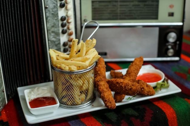 Kippenvingers met frites, ketchup, mayonaise, zoete chili saus, zijaanzicht