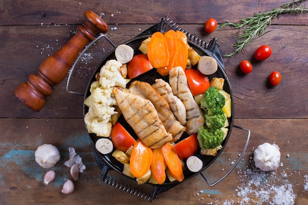 Kippenvlees en groenten op houten tafel
