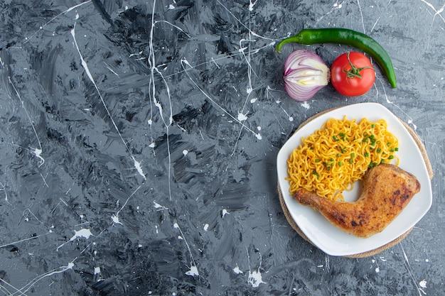 Kippenvlees en noedels op een bord op een onderzetter naast groenten, op de marmeren achtergrond.