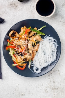 Kippenvlees met groentenwok en chinese rijstnoedels, sauzen en sesam in een zwarte kom met chinese eetstokjes bij lichtgrijze achtergrond. traditie aziatisch eten.