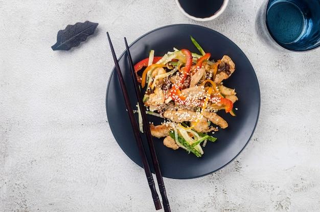 Kippenvlees met groentenwok en sauzen en sesam in een zwarte kom met chinese eetstokjes bij lichtgrijze achtergrond. traditie aziatisch eten.