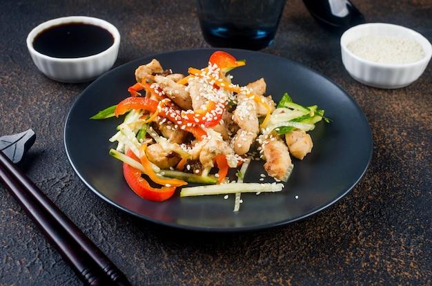 Kippenvlees met groentenwok, sojasausen en sesam in een zwarte plaat met chinese eetstokjes bij donkere achtergrond. traditie aziatisch eten. ruimte kopiëren