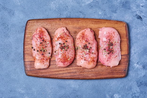 Kippenvlees met kruiden op een houten bord op blauw
