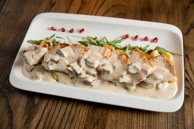 Kippenvlees op geraspte gnocchi in roomsaus van champignons en gerookte kaas