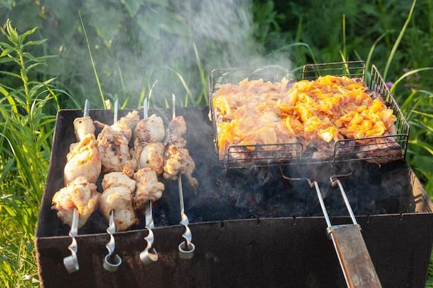 Kippenvlees wordt gebakken op de grill en op spiesjes een ijzeren kist met kolen in de tuin in de zomer