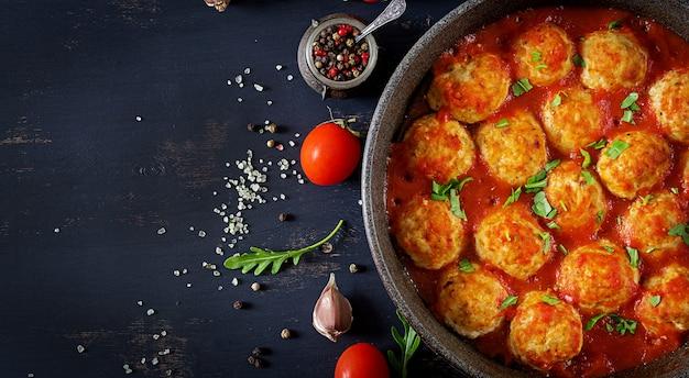Kippenvleesballetjes met tomatensaus in een pan. avondeten. bovenaanzicht donkere achtergrond.