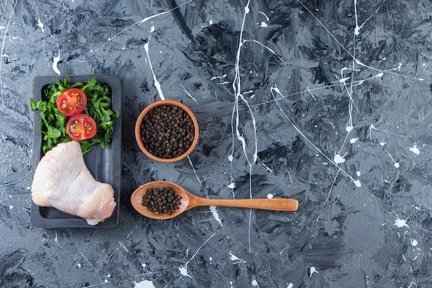 Kippenvleugel en groente op een bord naast kruidenkom en lepel, op de marmeren achtergrond.