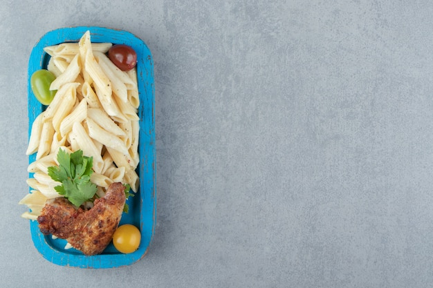 Kippenvleugel met penne pasta op blauw bord.