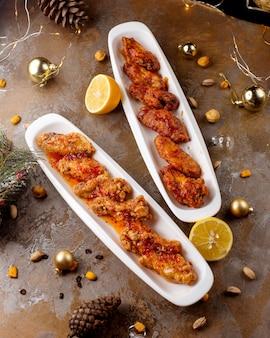Kippenvleugels en drumsticks bereid met saus en geserveerd met citroen