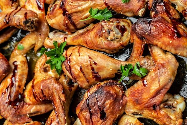 Kippenvleugels en poten met saus. vleugels van barbecue. bovenaanzicht, voedsel recept achtergrond. detailopname.