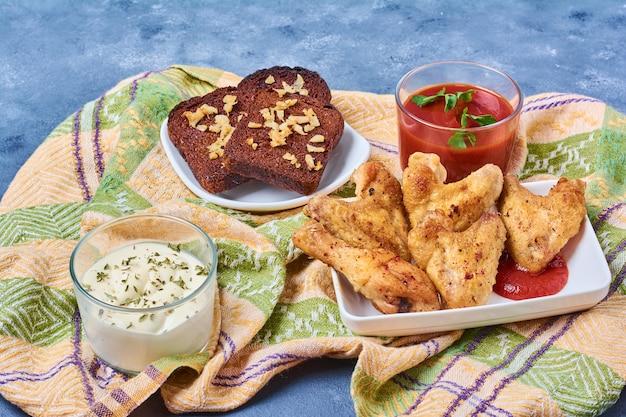 Kippenvleugels gebakken en geserveerd met sauzen.