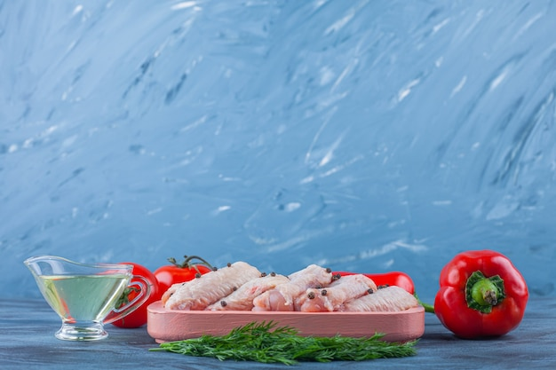 Kippenvleugels in een houten plaat naast tomaten en paprika, op de blauwe achtergrond.