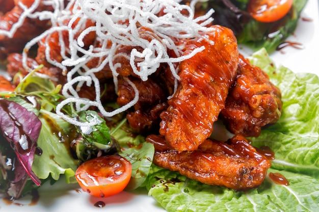 Kippenvleugels met barbecuesaus, salade, tomaten en chips op witte plaat