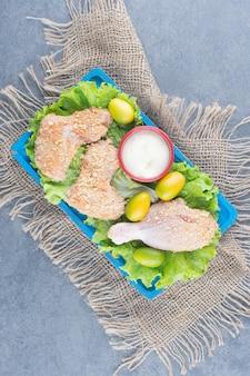 Kippenvleugels met broodkruimels en groenten op blauw bord.