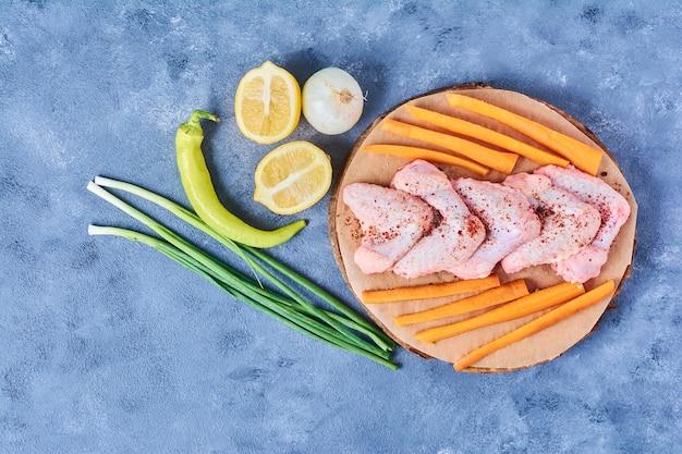 Kippenvleugels met groenten op een houten bord op blauw