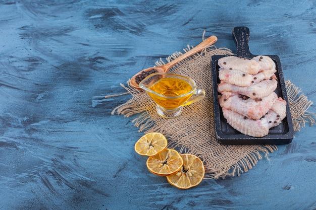 Kippenvleugels op een bord op een jute servet naast kom met olie, kruiden, lepel en gedroogde citroen, op de blauwe achtergrond.