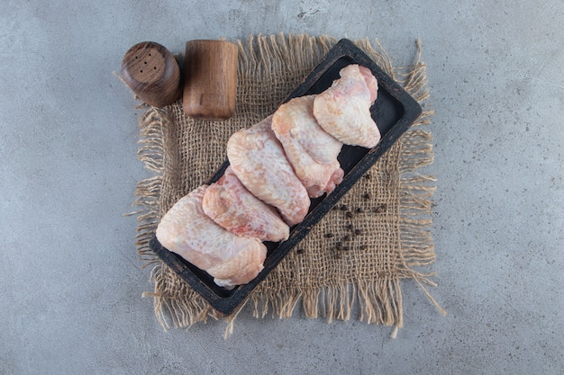 Kippenvleugels op een bord op een jute servet, op het marmeren oppervlak.