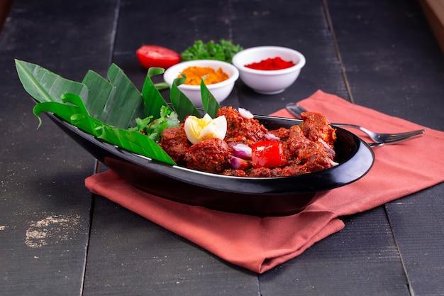Kipperalan of kip droge currykerala speciaal kipgerecht gerangschikt in een zwart servies