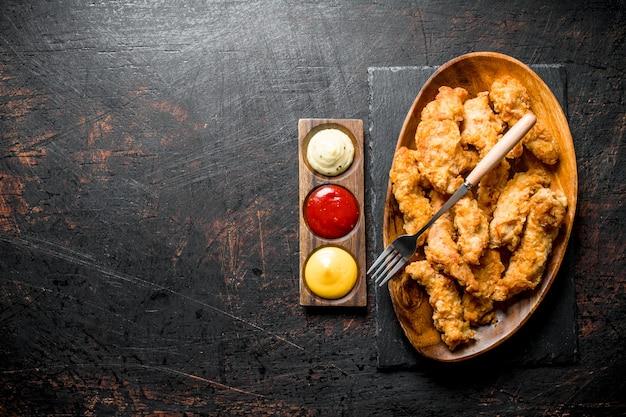 Kipreepjes op een bord met een vork en verschillende sauzen op donkere rustieke tafel.