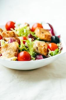 Kipsalade met cherrytomaatjes, sla en groenten voor gezonde voeding, bezorgservice voor eten en online bestelconcept