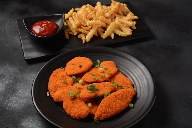 Kipschnitzel of nuggets met friet en ketchup