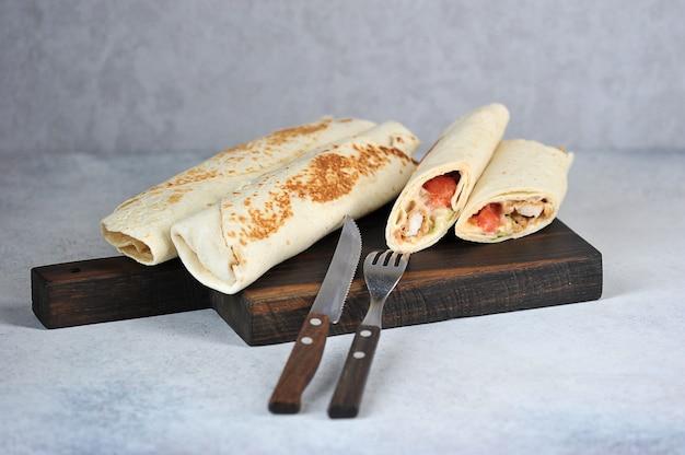 Kipshoarma op houten bord
