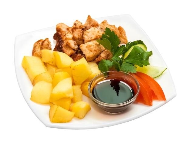 Kipspiesjes met gebakken aardappelen en verse groenten op een witte achtergrond. geïsoleerd object