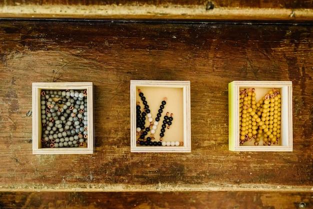 Kistjes met kralen om te leren rekenen in een montessorieklas op oud hout.