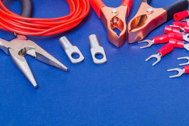 Kit reserveonderdelen en gereedschap, rode draden voor elektrisch voorbereid voor reparatie of plaatsing op een blauwe werkplaatstafel