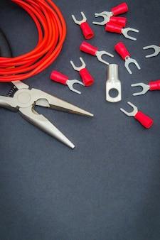 Kit reserveonderdelen en gereedschap, rode draden voor elektrisch voorbereid voor reparatie of plaatsing op een zwarte werkplaatstafel