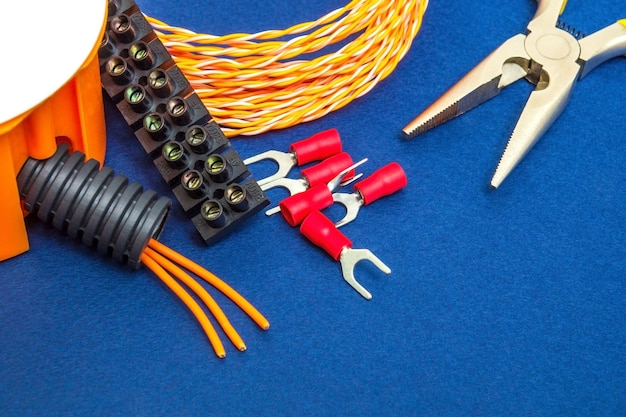Kit reserveonderdelen en gereedschappen, draden voor elektrisch voorbereid voor reparatie of instelling op een blauwe achtergrond