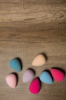 Kit van beauty blenders op een houten achtergrond. ruimte voor tekst